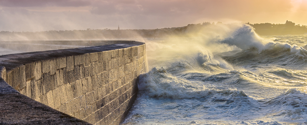Image of stormy seas battering a harbour wall